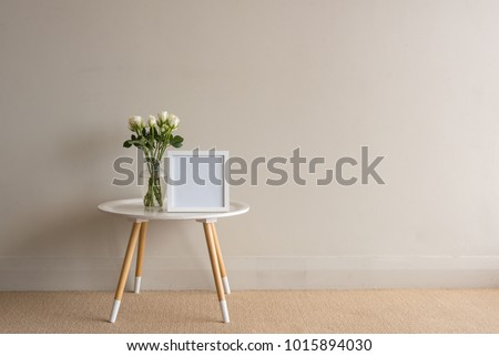 White roses in glass vase with blank square frame on small round table against beige wall
