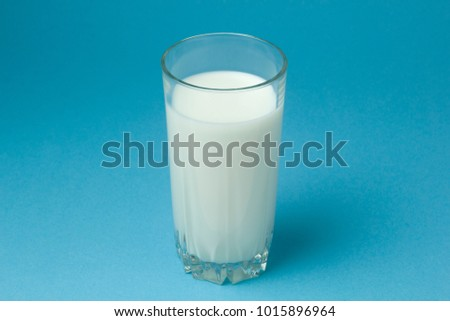 Milk in a glass on a blue background. Dairy. #1015896964