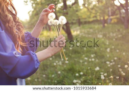 Young spring fashion woman blowing dandelion in spring garden. Springtime. Trendy girl at sunset in spring landscape background. Allergic to pollen of flowers. Spring allergy #1015933684