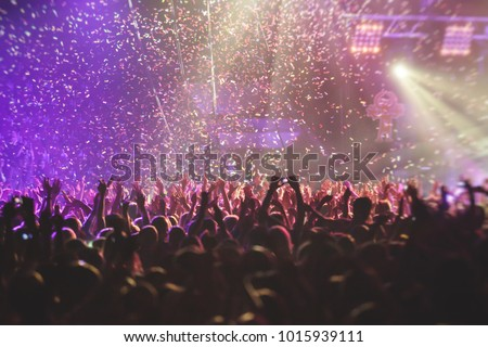 A crowded concert hall with scene stage lights, rock show performance, with people silhouette #1015939111