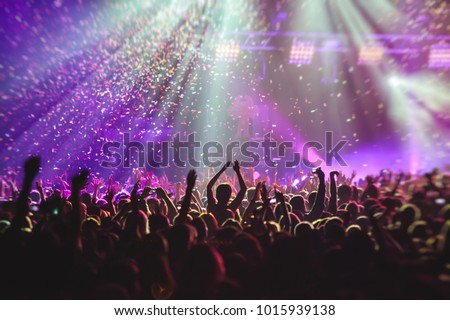 A crowded concert hall with scene stage lights, rock show performance, with people silhouette #1015939138