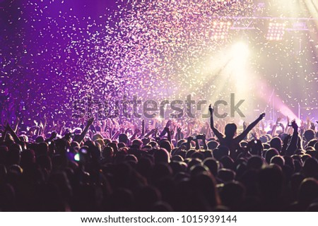 A crowded concert hall with scene stage lights, rock show performance, with people silhouette #1015939144
