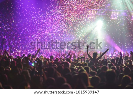 A crowded concert hall with scene stage lights, rock show performance, with people silhouette #1015939147