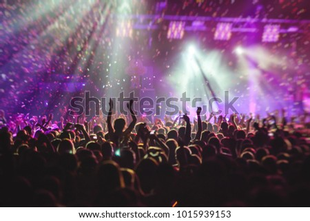 A crowded concert hall with scene stage lights, rock show performance, with people silhouette #1015939153