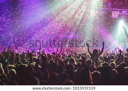 A crowded concert hall with scene stage lights, rock show performance, with people silhouette #1015939159