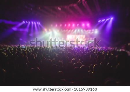 A crowded concert hall with scene stage lights, rock show performance, with people silhouette #1015939168
