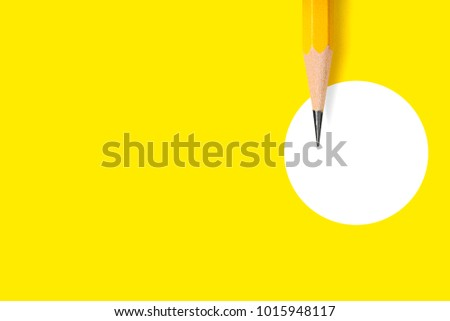 Minimalist template with copy space by top view close up macro photo of wooden yellow pencil isolated on yellow paper and combine with white circle. Flash light made smooth shadow from yellow pencil.