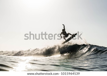 A silhouetted surfing airing on a wave breaking on a beach in puerto rico #1015964539