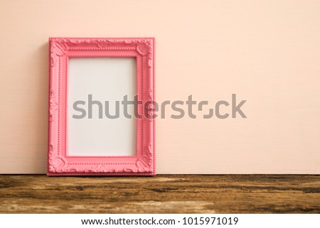 Pink vintage photo frame on old wooden table over pink wall background