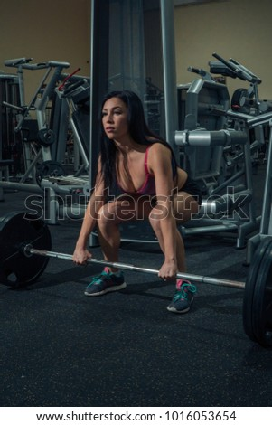 Portrait of a beautiful girl who crouches with a barbell in the gym. Sport life #1016053654
