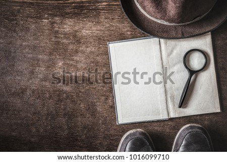 Opened old blank book with magnifying glass. Detective hat and shoes on brown background. Retro things. Historical atmosphere. Vintage english style. Evidence searching concept. Empty place for text. Royalty-Free Stock Photo #1016099710