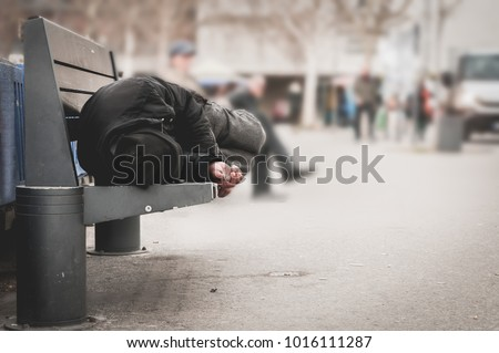 Poor homeless man or refugee sleeping on the wooden bench on the urban street in the city, social documentary concept, selective focus #1016111287
