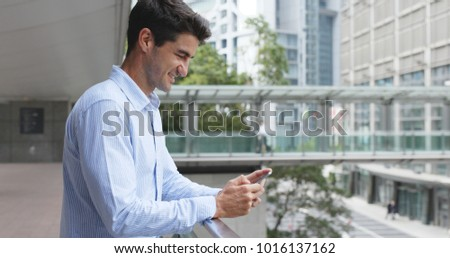 Businessman use of cellphone in Hong Kong city  #1016137162