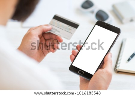 Closeup photo businessman holding hand credit card and using smartphone. Online payments plastic card. Horizontal mockup. Blurred, film effect