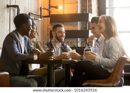 Multiracial friends having fun and laughing drinking coffee in coffeehouse, diverse young people talking joking sitting together at cafe table, multi ethnic millennials spending time in coffee shop Royalty-Free Stock Photo #1016243926