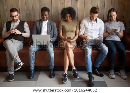 Multicultural young people using laptops and smartphones sitting in row, diverse african and caucasian millennials entertaining online obsessed with modern devices waiting in queue, gadget addiction #1016244052