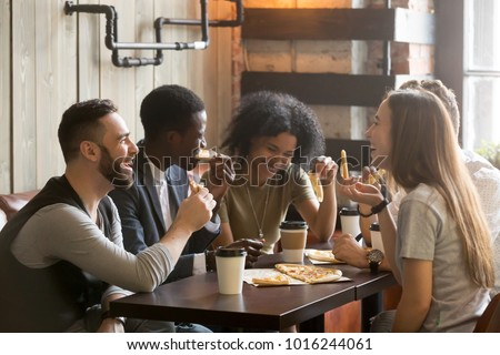 Multiracial happy young people eating pizza in pizzeria, black and white cheerful mates laughing enjoying meal having fun sitting together at restaurant table, diverse friends share lunch at meeting Royalty-Free Stock Photo #1016244061