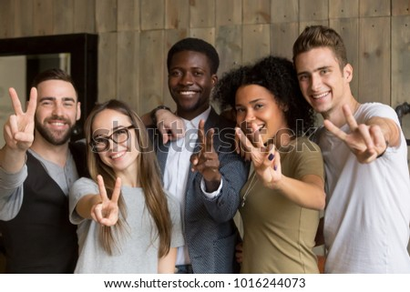 Happy multi ethnic young people looking at camera, smiling diverse friends or students showing peace sign, multicultural millennials posing together at meeting, tolerance and racial equality concept #1016244073