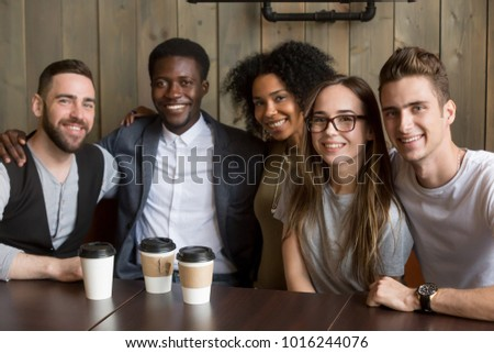 Portrait of multicultural millennial young friends looking at camera, happy multiracial people group having fun in coffeehouse together, diverse african and caucasian students bonding at cafe meeting #1016244076