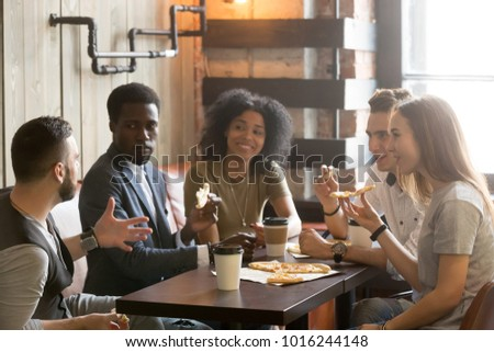 Multi-ethnic african and caucasian friends talking eating pizza in pizzeria, diverse young people enjoy italian food at meeting, multiracial students having conversation during lunch together in cafe #1016244148