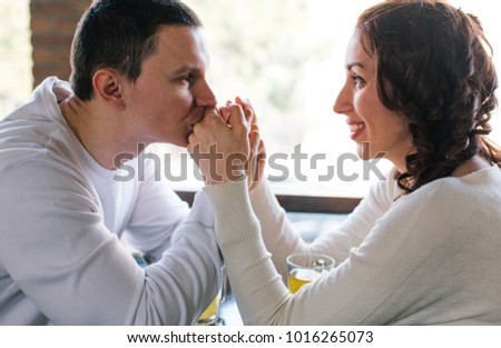 Young man kissing girlfriend's hands. Couple in love #1016265073