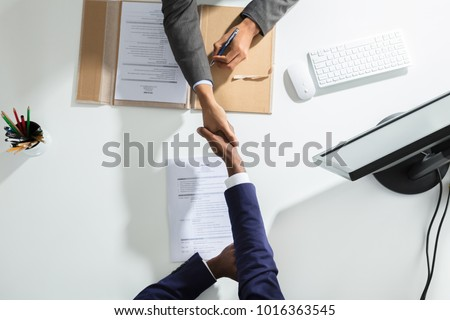 High Angle View Of Businessperson Shaking Hand With Candidate Over White Desk Royalty-Free Stock Photo #1016363545