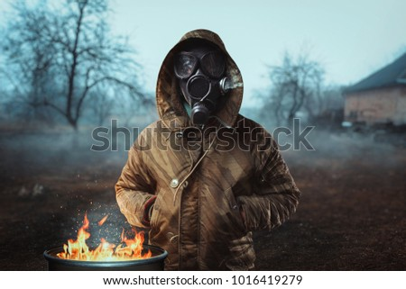 Stalker soldier in gas mask against fire, doomsday Royalty-Free Stock Photo #1016419279