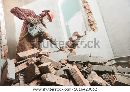 worker with demolition hammer breaking interior wall Royalty-Free Stock Photo #1016423062