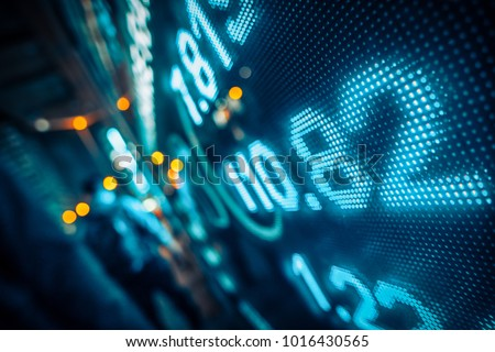 Financial stock market numbers and city light reflection Royalty-Free Stock Photo #1016430565