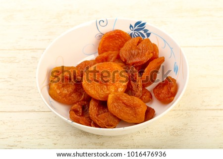 Dried apricots heap in the bowl over wooden background #1016476936