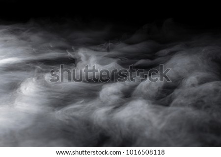 Swirling from bottom left clouds of dry ice fog blowing Royalty-Free Stock Photo #1016508118