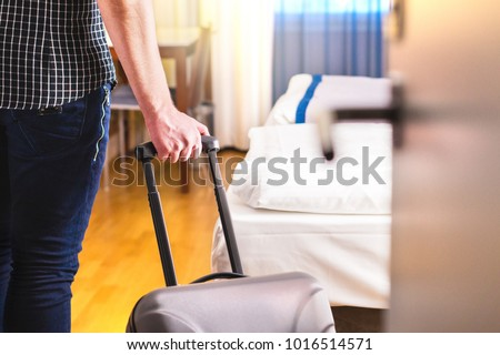 Man pulling suitcase and entering hotel room. Traveler going in to room or walking inside motel with luggage. Travel and holiday apartment rental concept. #1016514571