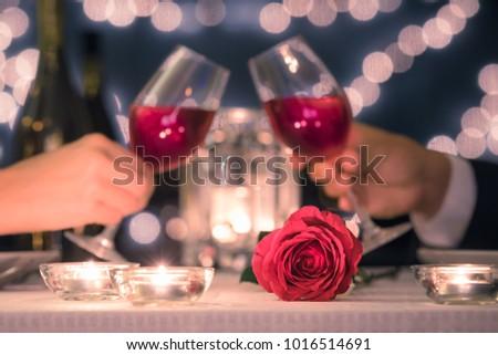 Couple enjoying romantic candle light dinner.  Focus on rose.   #1016514691