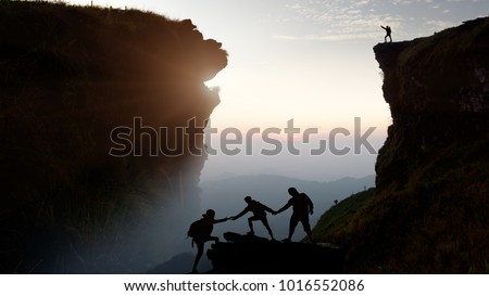 Male hiker celebrating success on top of a mountain in a majestic sunrise and Climbing group friends helping hike up .Teamwork , Helps ,Success, winner and Leadership concept . #1016552086