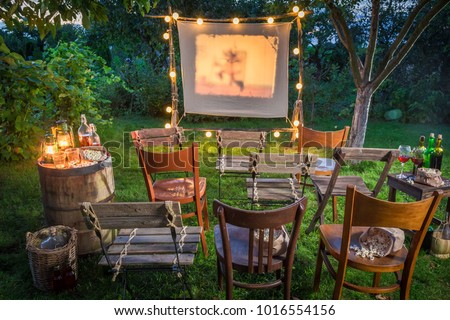 Summer cinema with retro projector in the garden Royalty-Free Stock Photo #1016554156