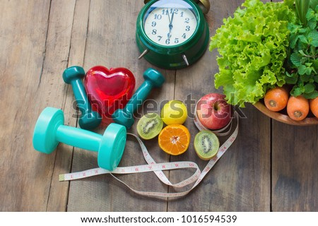 Healthy food concept, fruits and vegetables, apple, kiwi, lemon, carrots and green vegetables dumbbell for weight loss exercises. Red heart and Measuring tape and alarm clock on wooden background #1016594539