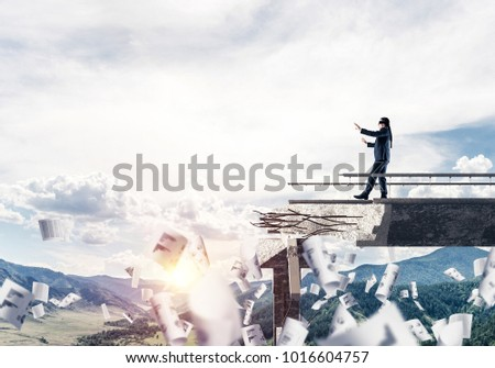 Businessman walking blindfolded among flying papers on concrete bridge with huge gap as symbol of hidden threats and risks. Skyscape and nature view on background. 3D rendering. #1016604757