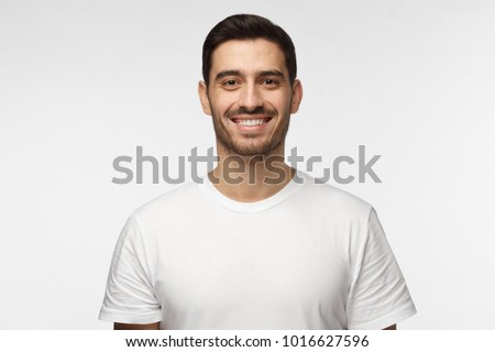 Close up portrait of smiling handsome man in white t-shirt looking at camera, isolated on gray background #1016627596