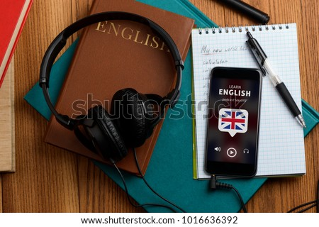 Listening to English speech. Using podcast app and headphones for better learning and improving vocabulary with new words. Royalty-Free Stock Photo #1016636392