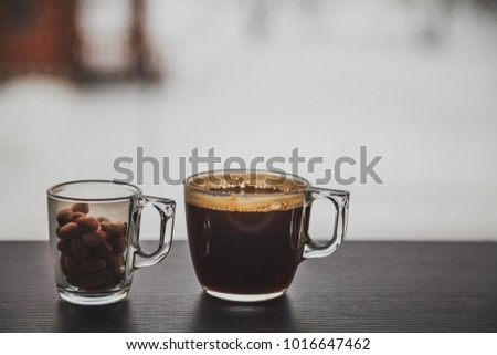 Transparent cup of coffee and a small glass cup filled with peanuts placed on dark brown laminated wooden surface in front of a window. #1016647462