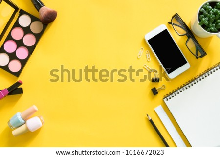 Creative workplace with mock up smartphone,office accessories and cosmetics on yellow background. #1016672023