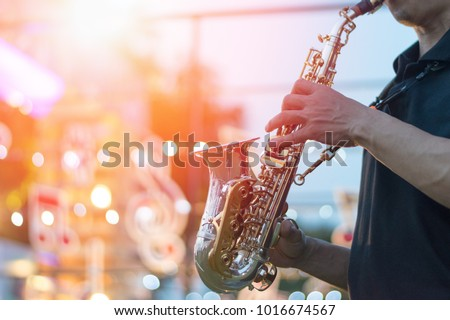 jazz festival. Saxophone, music instrument played by saxophonist player musician in fest. #1016674567