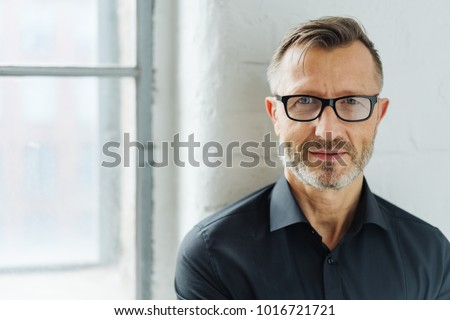 Bearded middle-aged man wearing glasses looking at camera with a serious expression in a close up head and shoulders portrait
