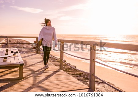 Girl holding a skateboard  near the beach at sunset. #1016761384