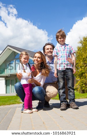 Portrait of happy smiling family and their children near their house #1016863921