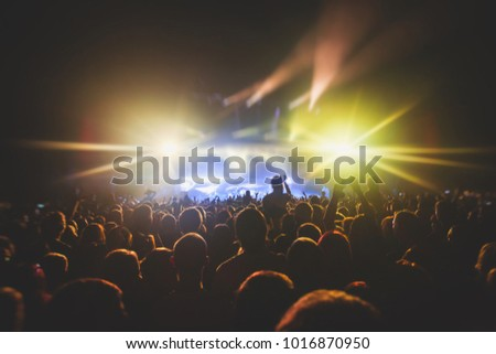 A crowded concert hall with scene stage lights, rock show performance, with people silhouette #1016870950