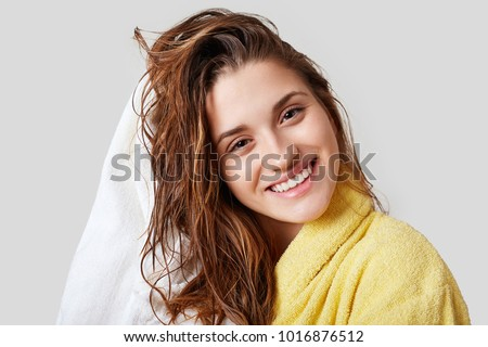 Lovely female with wet hair, takes shower, dries head with towel, being pleased after taking bath, dressed in yellow bathrobe, poses against white background, has cheerful expression #1016876512
