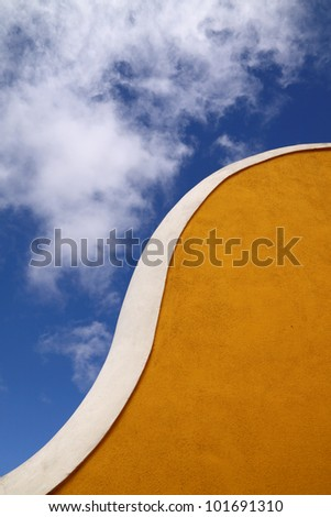 Portugal Lisbon Oeiras Architectural detail - curved yellow stucco wall with white piped border against a blue sky with wispy clouds #101691310