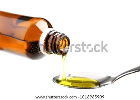 Bottle pouring medical syrup in spoon on white background #1016965909