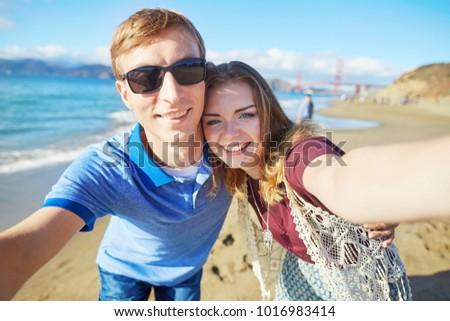 Romantic loving couple taking selfie in San Francisco, California, USA. Golden gate bridge in the background #1016983414
